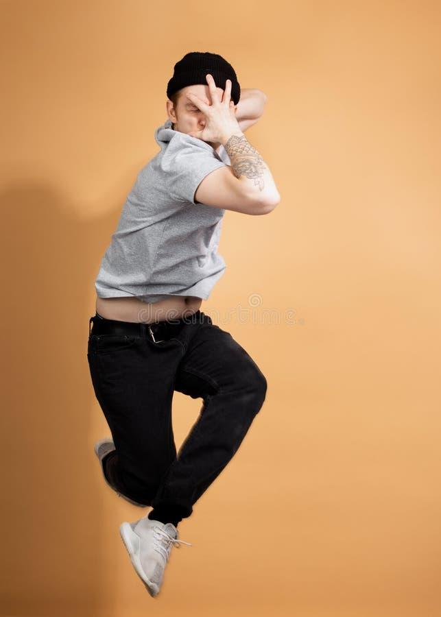 De modieuze kerel gekleed in een grijs overhemd, zwarte jeans en een zwarte hoed met tatoegering op zijn hand springt op het beig stock afbeelding