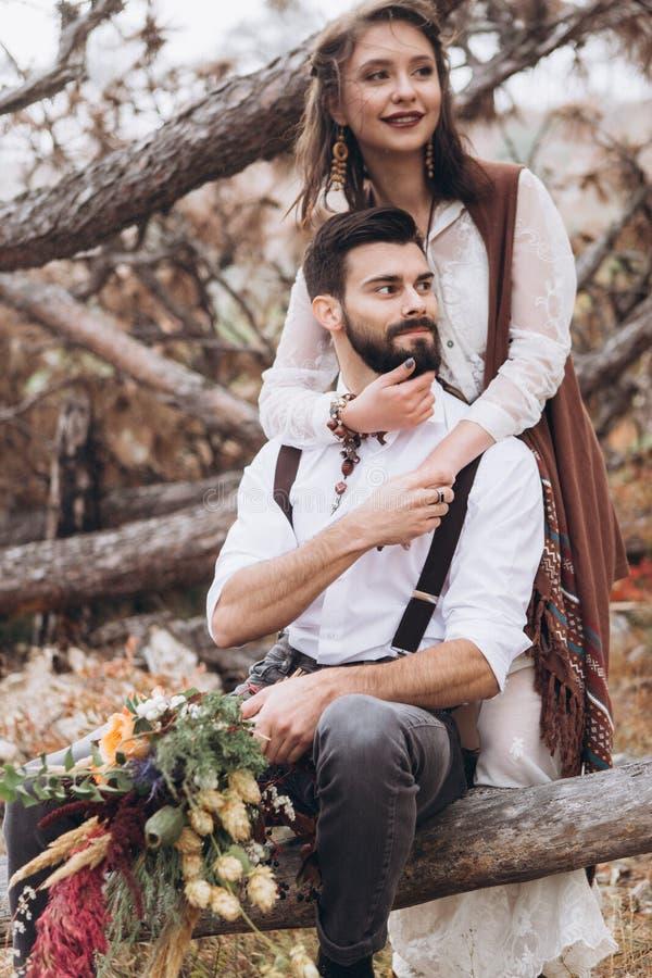 De modieuze kerel met een baard koestert een meisje gekleed in een kleding in de stijl van boho stock foto