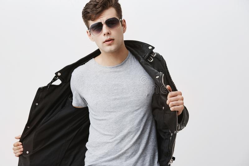 De modieuze knappe aantrekkelijke Europese jonge mens met in kapsel kleedde zich in in zwart leerjasje, het dragen royalty-vrije stock afbeeldingen
