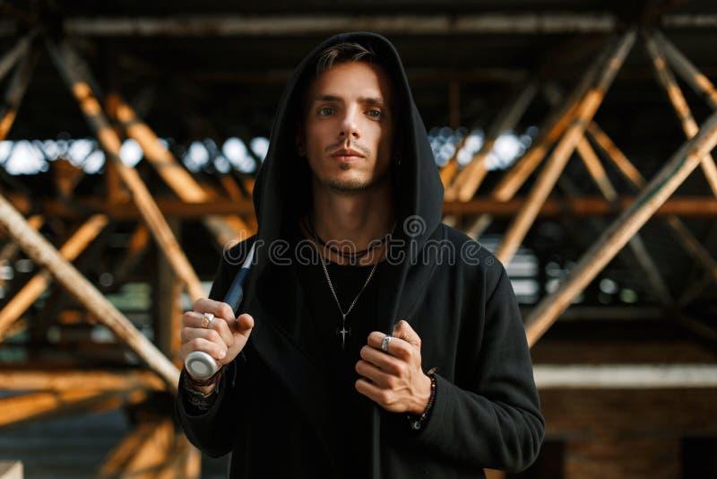 De modieuze knappe mens in een zwarte robe met een kap houdt een knuppel stock foto