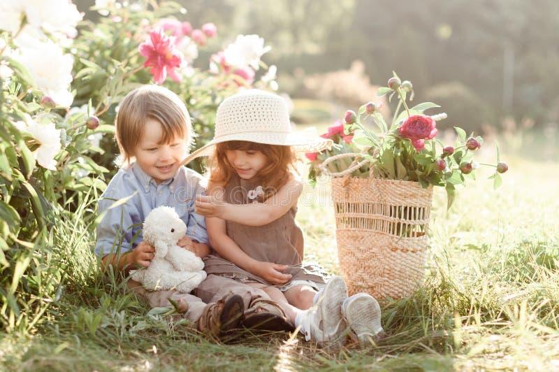 De modieuze leuke het kinderenjongen en meisje zitten dichtbij pioenenbloemen royalty-vrije stock foto's