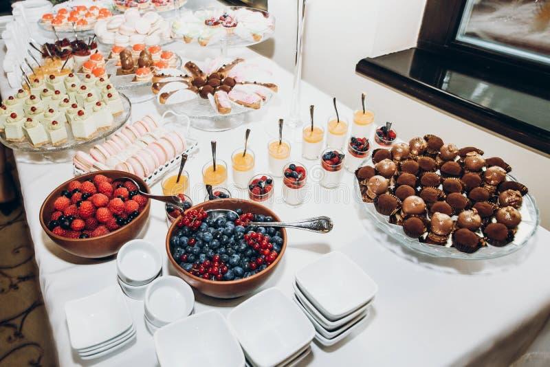 De modieuze lijst van de suikergoedbar met heerlijke cakes, koekjes, cupcakes met vruchten en bessen luxecatering in restaurant m stock foto's