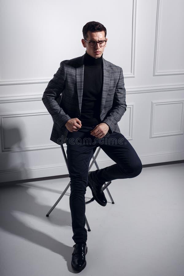 De modieuze mens in elegant kostuum, zwarte oogglazen zit op zwarte stoel en kijkt ernstig in één richting royalty-vrije stock foto