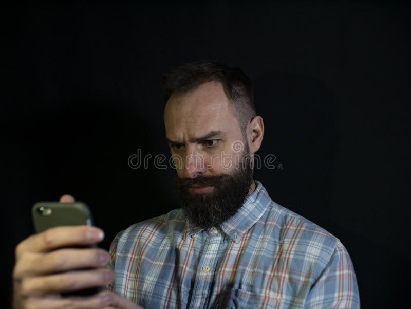 De modieuze mens met een baard en een snor bekijkt een mobiele telefoon met een ernstige gelaatsuitdrukking op een zwarte achterg royalty-vrije stock afbeelding