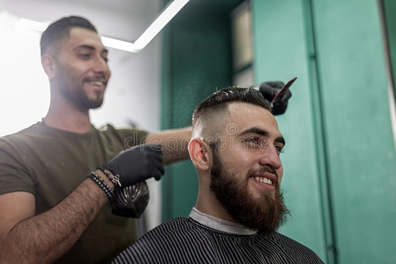 De modieuze mens met een baard zit en glimlacht bij een kapperswinkel De kapper in zwarte handschoenen doet het bespuiten voor ka royalty-vrije stock foto's