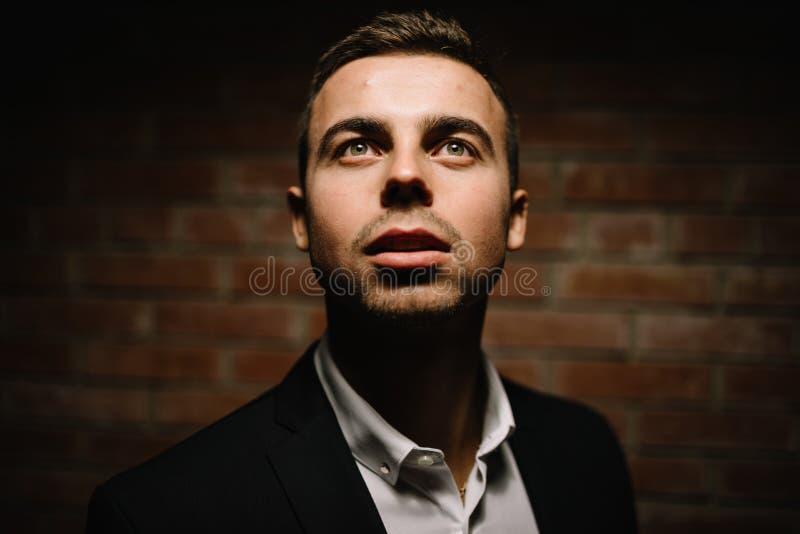 De modieuze mens op een zwarte achtergrond houdt van hem het gezicht indienen stock foto's