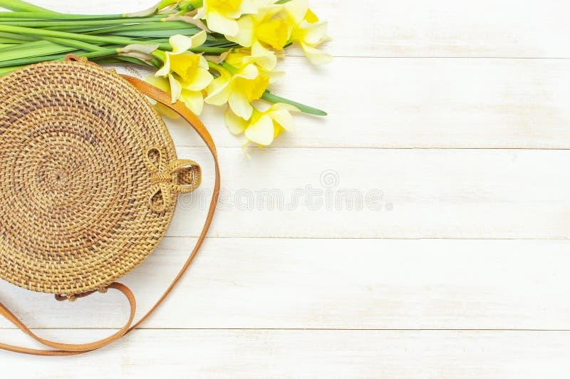 De modieuze met de hand gemaakte natuurlijke organische ronde rotanzak, de gele narcissen of de gele narcisbloemen op lichte hout royalty-vrije stock fotografie