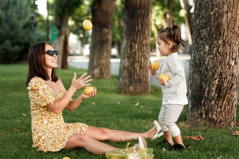 De modieuze moeder jongleert met citroenen voor haar dochterzitting op het gras stock afbeeldingen