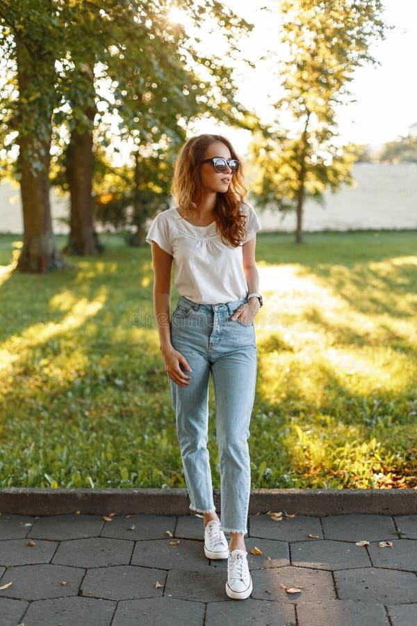 De modieuze mooie hipster jonge vrouw in een witte T-shirt in modieuze uitstekende jeans in in zonnebril in tennisschoenen loopt royalty-vrije stock foto