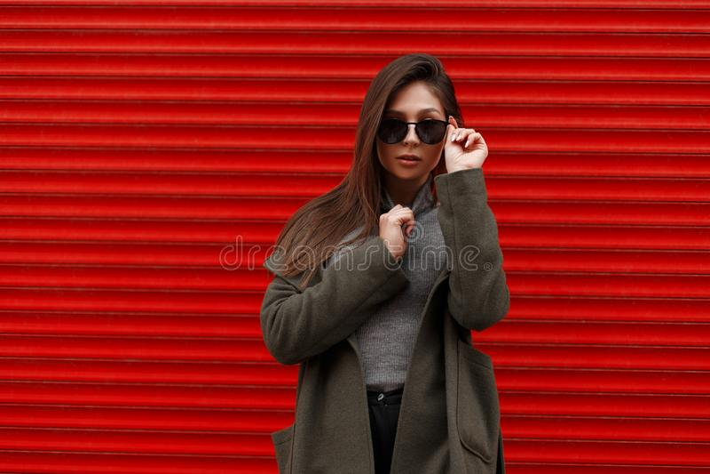 De modieuze mooie jonge vrouw in een groene manierlaag en een grijze sweater maakt modieuze zonnebril dichtbij de rode metaalmuur stock fotografie