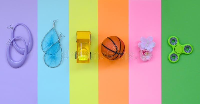 De in modieuze pastelkleursamenstelling met oorringen, zonnebril, drank kan, basketbalbal, stuk speelgoed vrachtwagen, bloem en s royalty-vrije stock foto