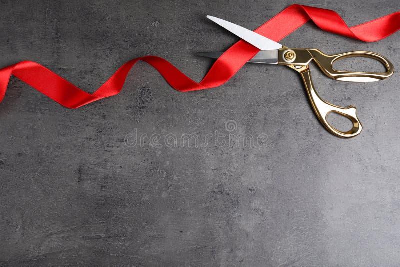 De modieuze schaar en het rode lint op grijze vlakke achtergrond, leggen Plechtig bandknipsel royalty-vrije stock afbeeldingen