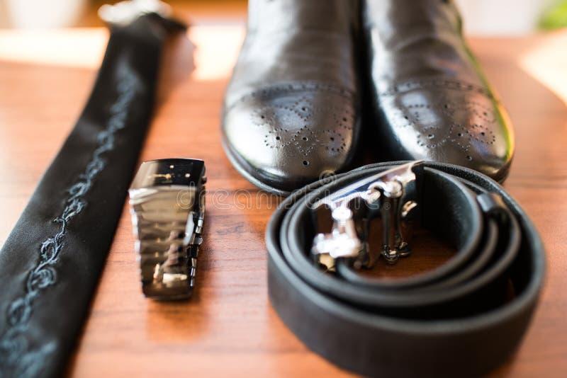 De modieuze schoenen van leermensen ` s in nadruk, horloge, band, riem voor bruidegom Huwelijkstoebehoren op rustieke bruine hout stock afbeelding