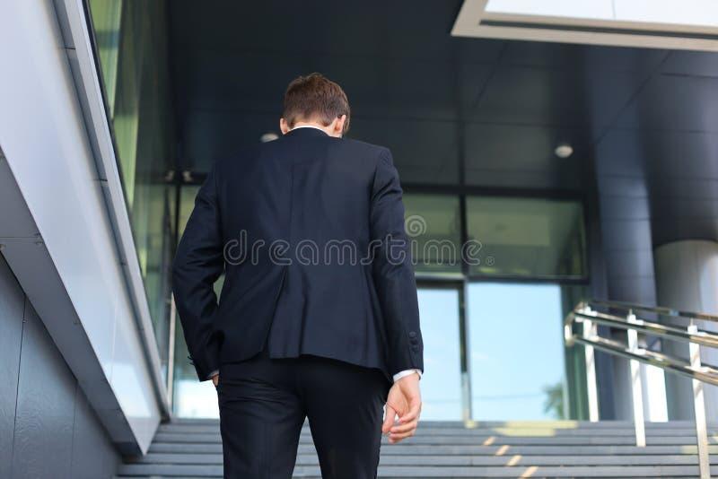 De modieuze succesvolle zakenman gaat de treden van het bureaugebouw uit royalty-vrije stock afbeeldingen