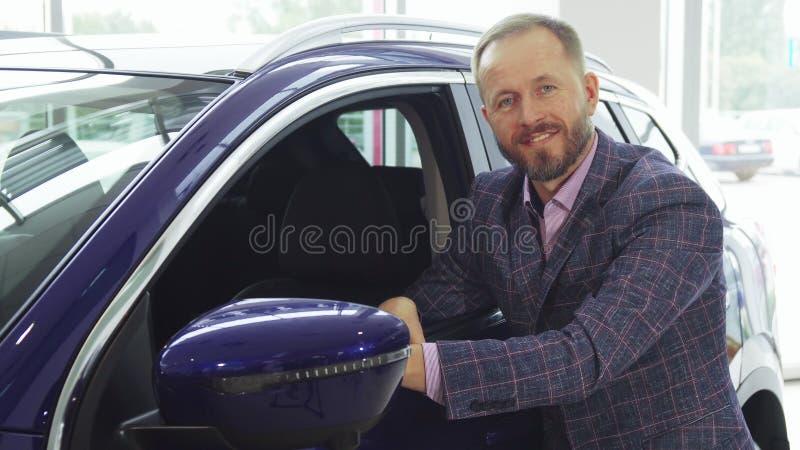 De modieuze verkoper bewondert de auto royalty-vrije stock fotografie