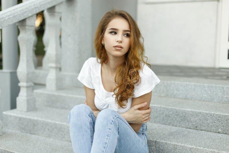 De modieuze vrij Europese jonge vrouw in een witte modieuze t-shirt in blauwe modieuze jeans rust op de uitstekende trede royalty-vrije stock foto's