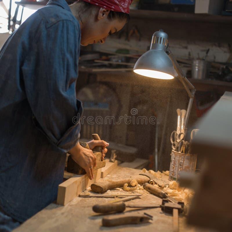 De modieuze vrouw in jeans kleedt de werken in de winkel Hulpmiddel voor hout stock foto