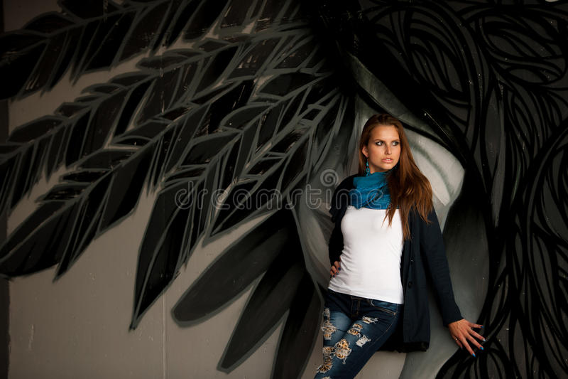 De modieuze vrouw met blured graffitti op achtergrond stock afbeelding