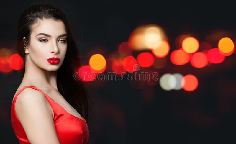 De modieuze vrouw met rode lippenmake-up op achtergrond met abstracte nacht schittert fonkeling stock foto