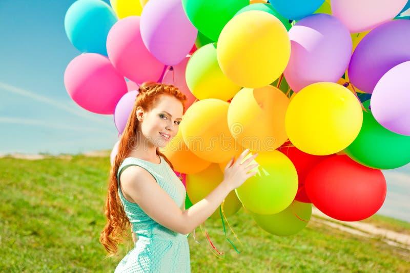 De modieuze vrouw van de luxemanier met ballons in hand op het gebied royalty-vrije stock afbeelding