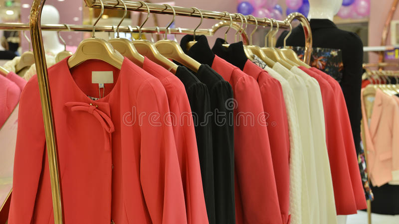 De modieuze vrouwen kleden zich op hangers in kledingswinkel stock fotografie