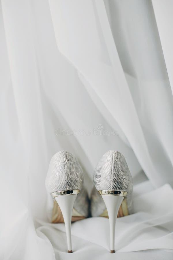 De modieuze witte schoenen voor bruid op wit Tulle in zachte ochtend steken in hotelruimte aan Ochtendvoorbereiding vóór huwelijk stock afbeeldingen