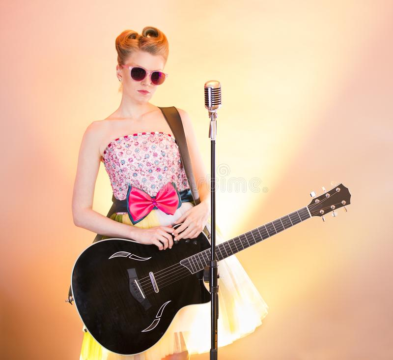 De modieuze zanger van de meisjesgitarist in roze glazen met zwarte gitaar, uitstekende microfoon Tienermusicus in grappige wijno royalty-vrije stock afbeelding