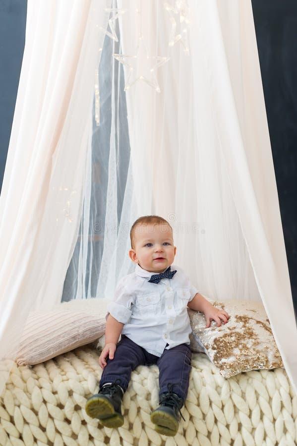 De modieuze zitting van de babyjongen in de slaapkamer met een gordijn stock foto's