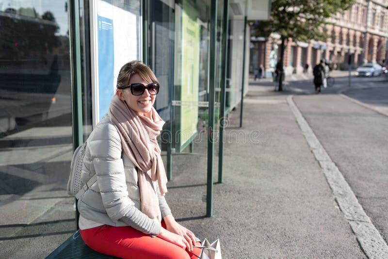 De modieuze zitting van het hipstermeisje op bushalte in de lente zonnige dag modieuze vrouwentoerist die op stadsvervoer wachten stock afbeelding