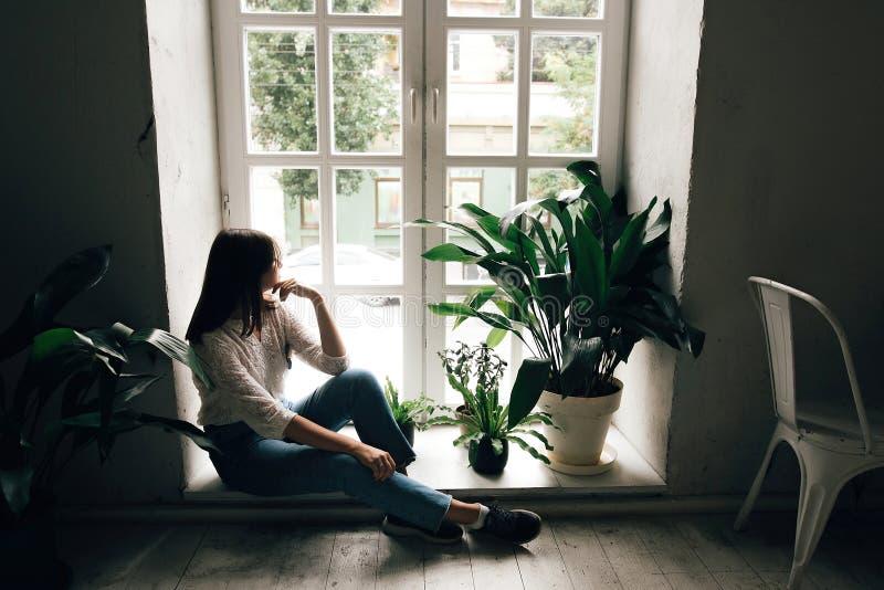 De modieuze zitting van het hipstermeisje op vloer en het bekijken wit rustiek venster met groene installaties in moderne koffie  stock foto's