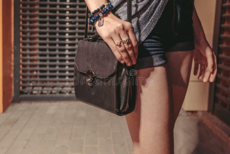 De modieuze zwarte handtas met wapen op zijn bovenkant, hipster meisje het stellen dichtbij de deur van de nachtclub sloot met me stock afbeeldingen
