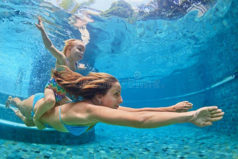 De moeder, babymeisje zwemt en duikt onderwater in pool stock afbeelding