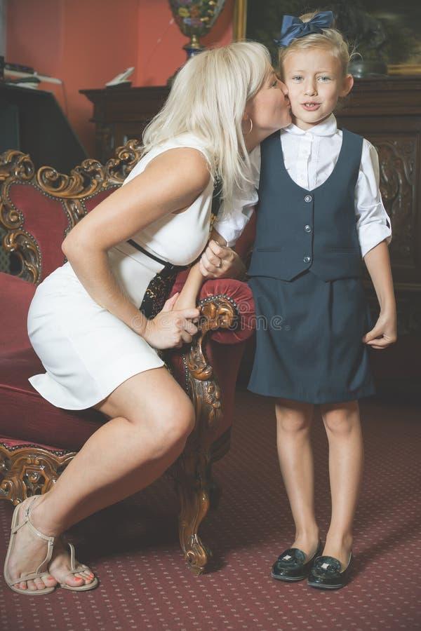 De moeder begeleidt dochter aan school en kust haar stock afbeeldingen