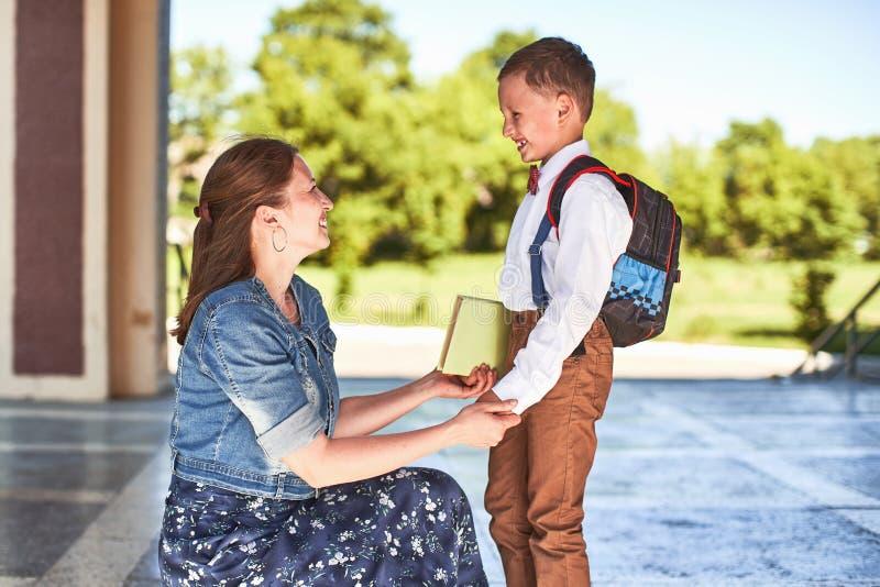 De moeder begeleidt het kind aan school het mamma moedigt student aan die hem begeleiden aan school een gevende moeder bekijkt te royalty-vrije stock afbeelding