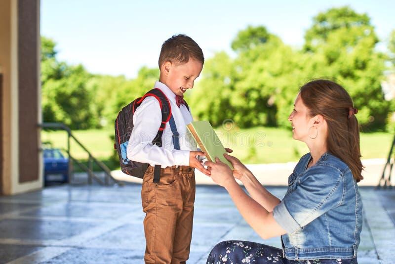 De moeder begeleidt het kind aan school het mamma moedigt student aan die hem begeleiden aan school een gevende moeder bekijkt te stock foto's