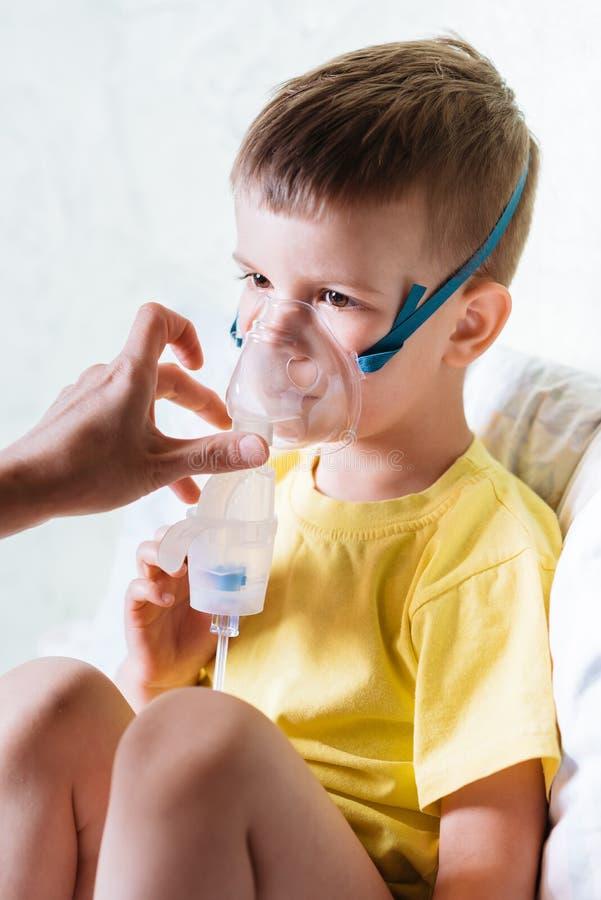 De moeder behandelt bronchitis in een kind met een verstuiver stock afbeeldingen