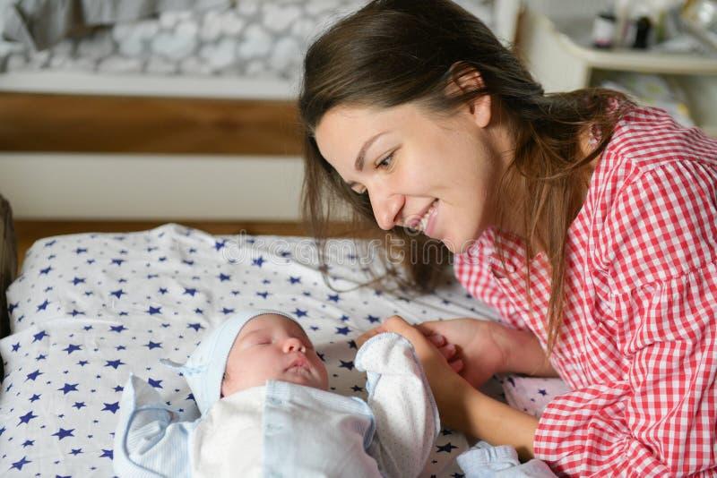 De moeder bekijkt haar kind Jonge moeder die op haar pasgeboren baby kijken Mooi mamma die bij bed met een leuke nieuwe slaap lig royalty-vrije stock fotografie