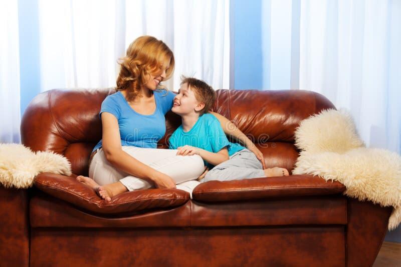 De moeder bekijkt kindzitting op laag stock foto