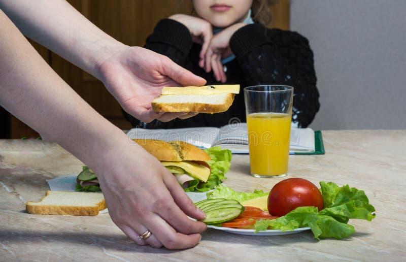 De moeder bereidt een sandwich voor een kind in school, sandwich voor royalty-vrije stock foto's