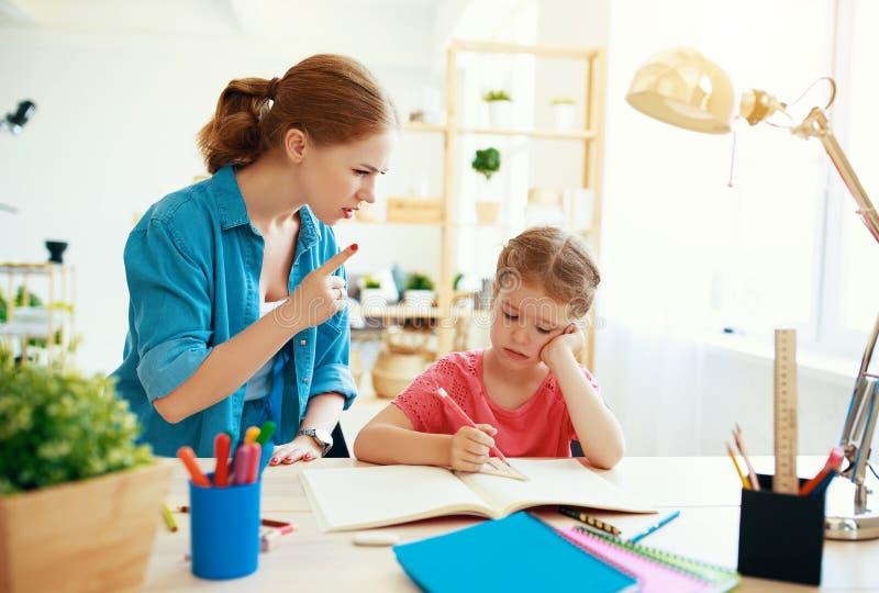 De moeder berispt een kind voor het slecht scholen en thuiswerk stock foto
