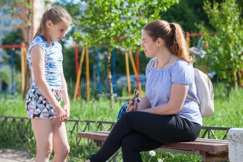 De moeder blaast - omhoog haar jonge dochter voor slecht gedrag terwijl het lopen op speelplaats royalty-vrije stock foto