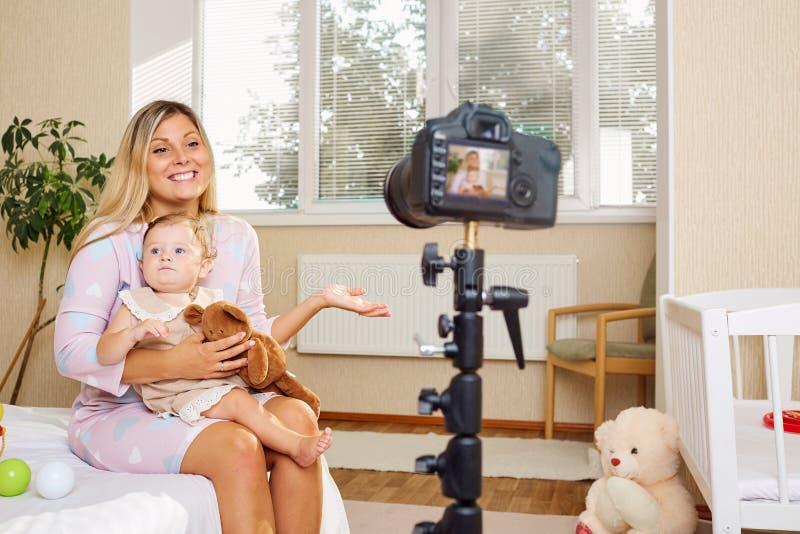 De moeder blogger registreert de video op de camera met de binnen baby royalty-vrije stock fotografie