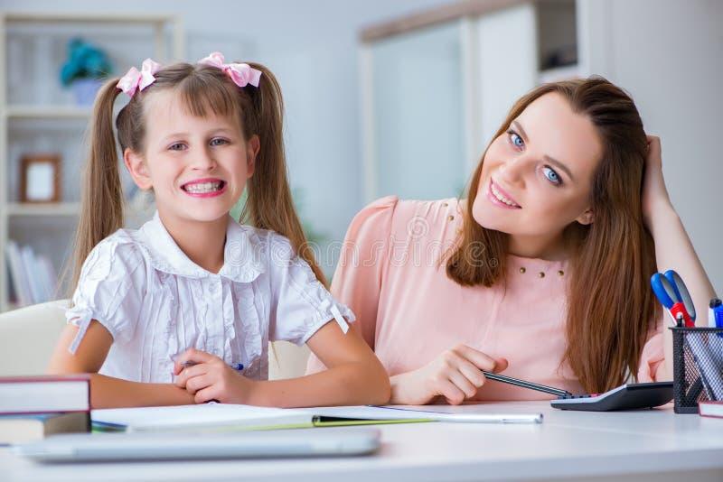 De moeder die haar dochter helpen om thuiswerk te doen stock afbeelding