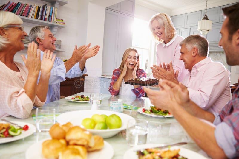 De moeder dient Verjaardagscake aan Volwassen Dochter bij Familiemaaltijd stock afbeelding