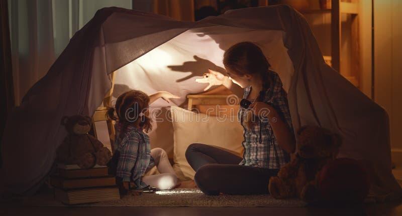 De moeder doet schrikken kind vertelt enge verhalen, speelt in theater van sha royalty-vrije stock afbeelding