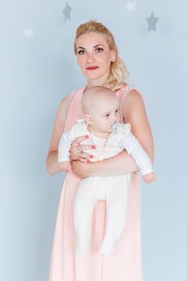 De moeder in een roze kleding houdt een kleine zoon in haar wapens en onderzoekt de camera stock afbeeldingen