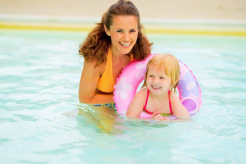 De moeder en de baby met zwemmen ring die in pool zwemmen royalty-vrije stock afbeelding
