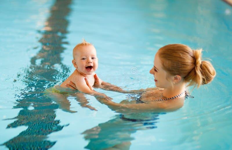 De moeder en de baby zwemmen in pool stock foto's