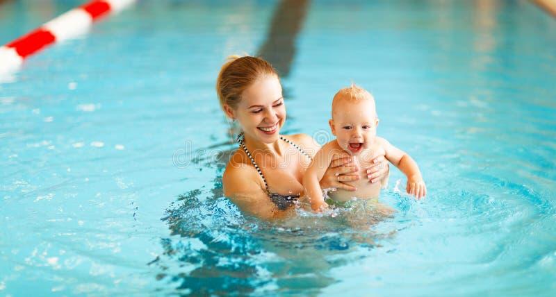 De moeder en de baby zwemmen in pool stock fotografie