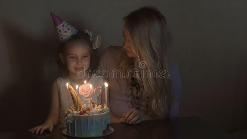 De moeder en de dochter blazen uit kaarsen op een verjaardag cake en het maken van een wens de verjaardag van een klein meisje royalty-vrije stock foto